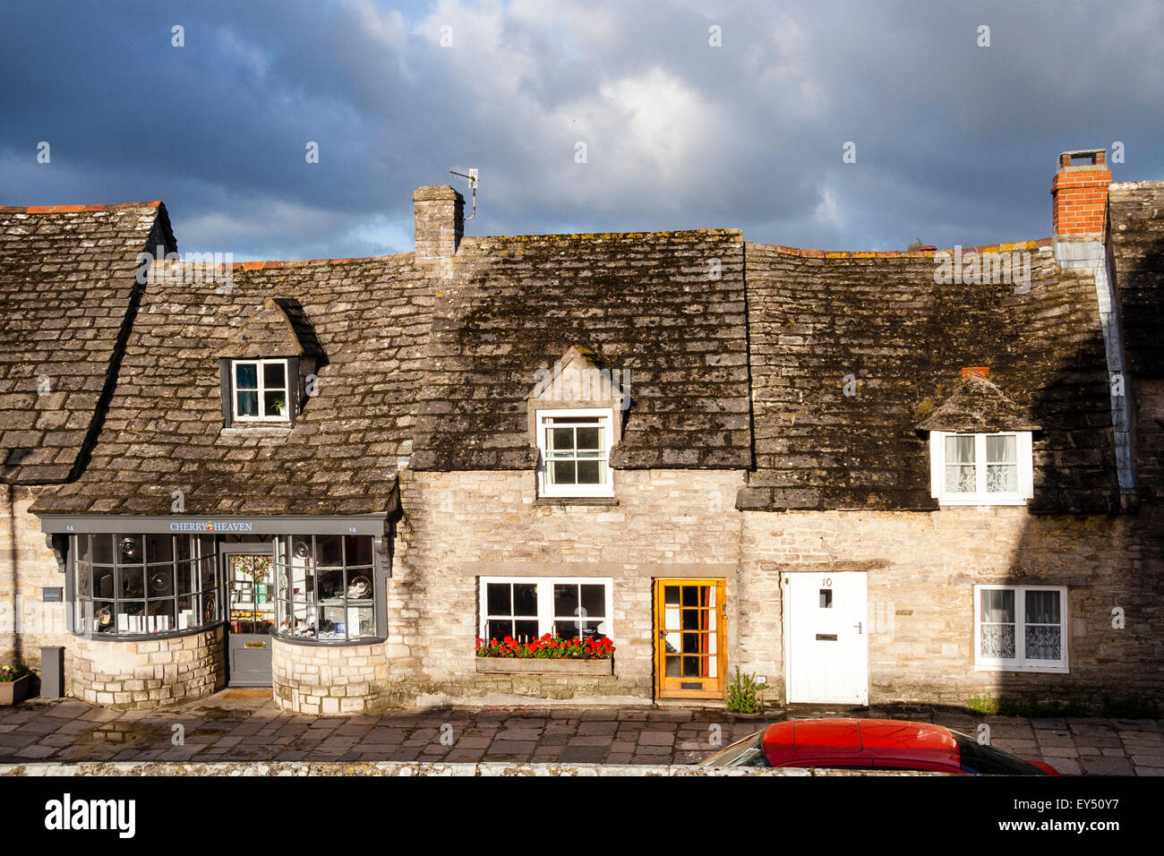 Typical old world English village scene, row of cottages with uneven roofs, Corfe, Dorset, dark skies, viewed head - Stock Image