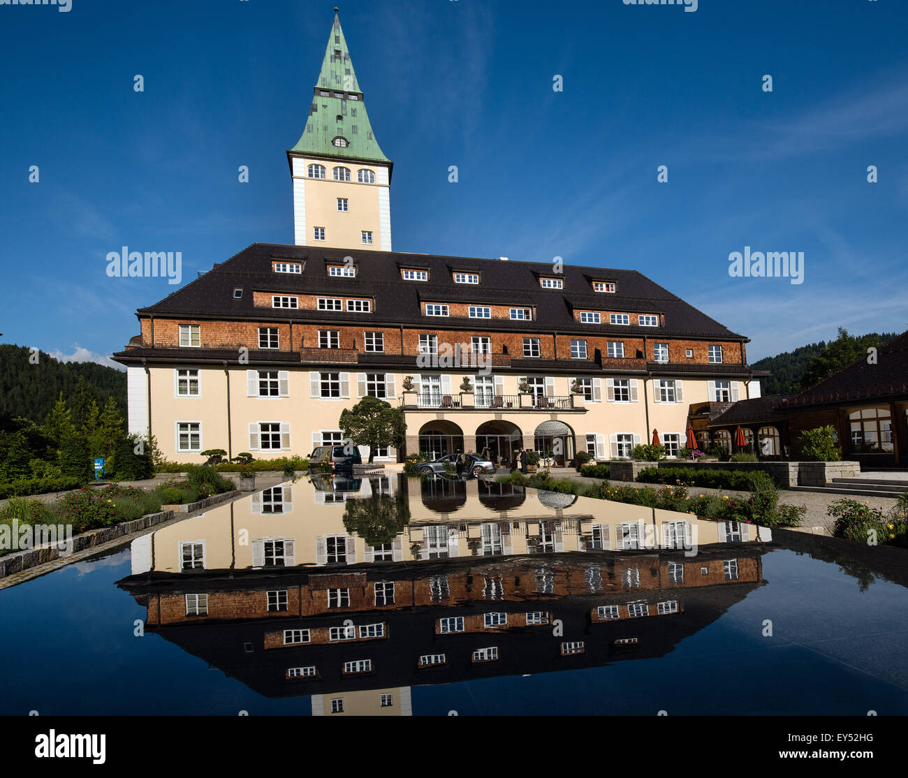 Schloss Elmau Castle Hotel with tower, reflected in the fountain basin, Wetterstein mountains, Klais, Krün, - Stock Image
