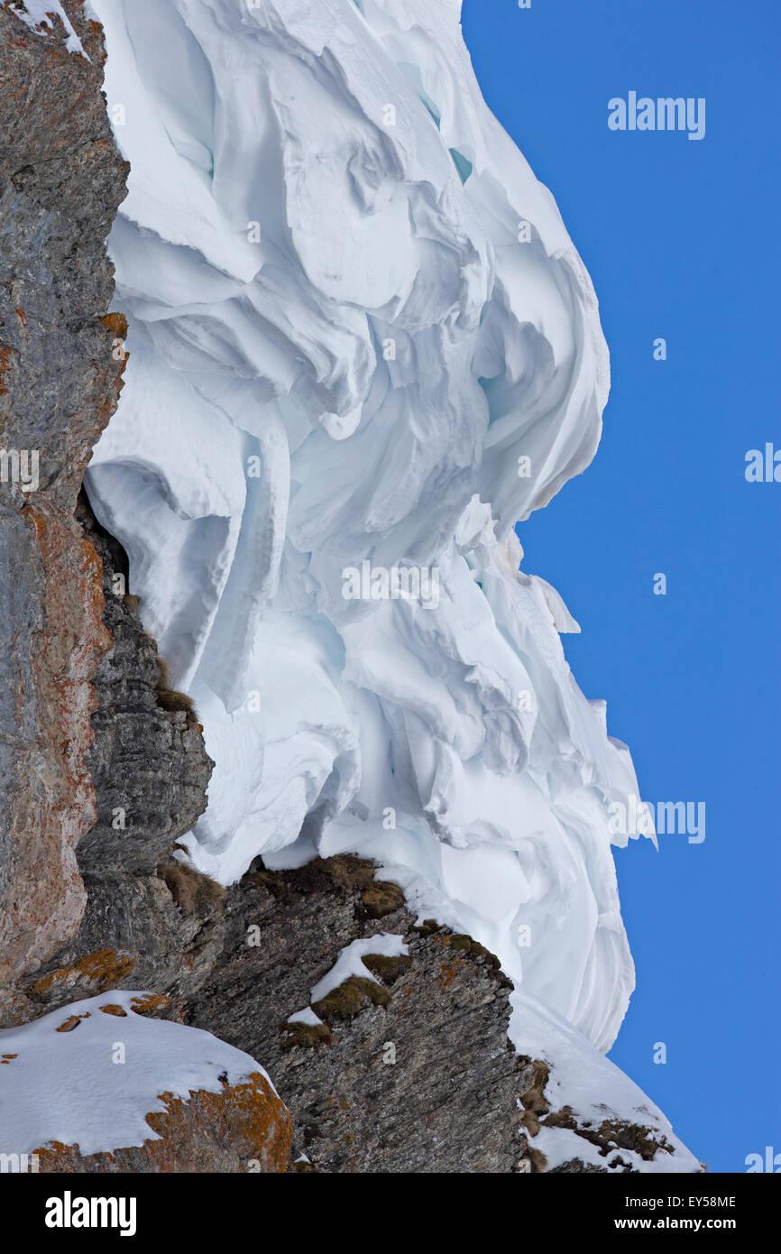 Snowdrift on rock - Swiss Alps - Stock Image