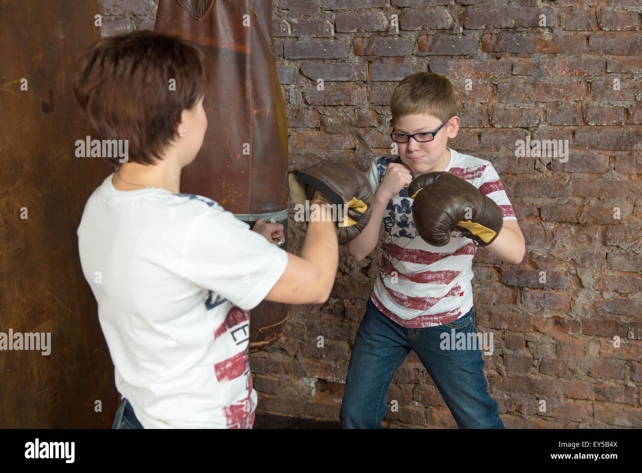 Mother and son - teenager about punching bag - Stock Image