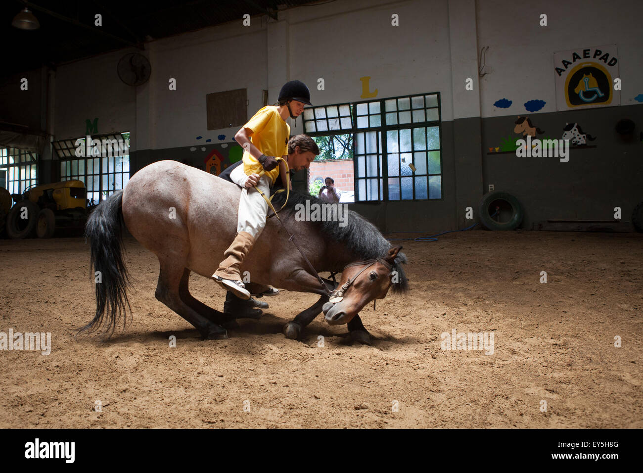 Child performing a balancing act on a horse lying Emmanuel 13 years with cerebral palsy comes to the center every - Stock Image
