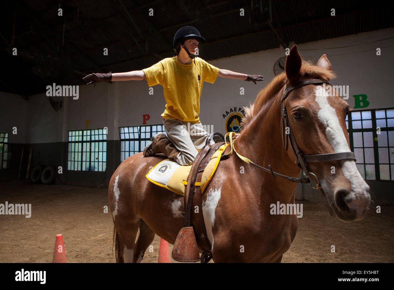 Child performing a balancing act on a horse Emmanuel 13 years with cerebral palsy comes to the center every week - Stock Image