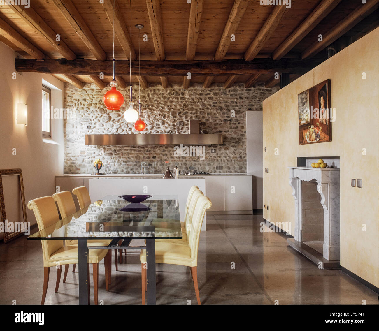 dining table made of glass and chairs neat to fireplace overlooking on the modern kitchen  whose floor is with marble - Stock Image