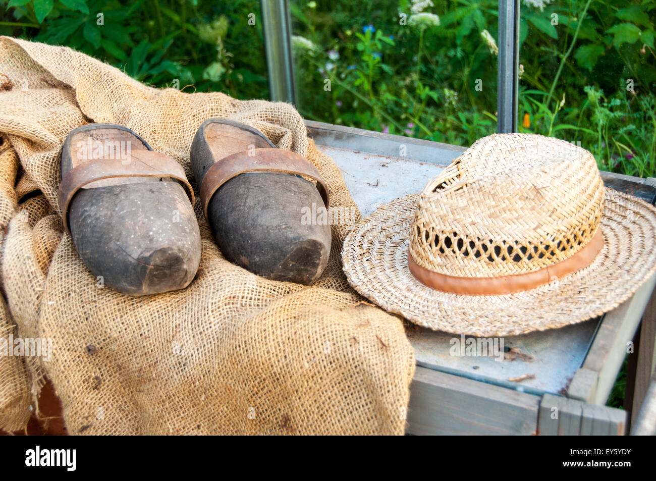 Hat and garden clogs on hessian - Stock Image