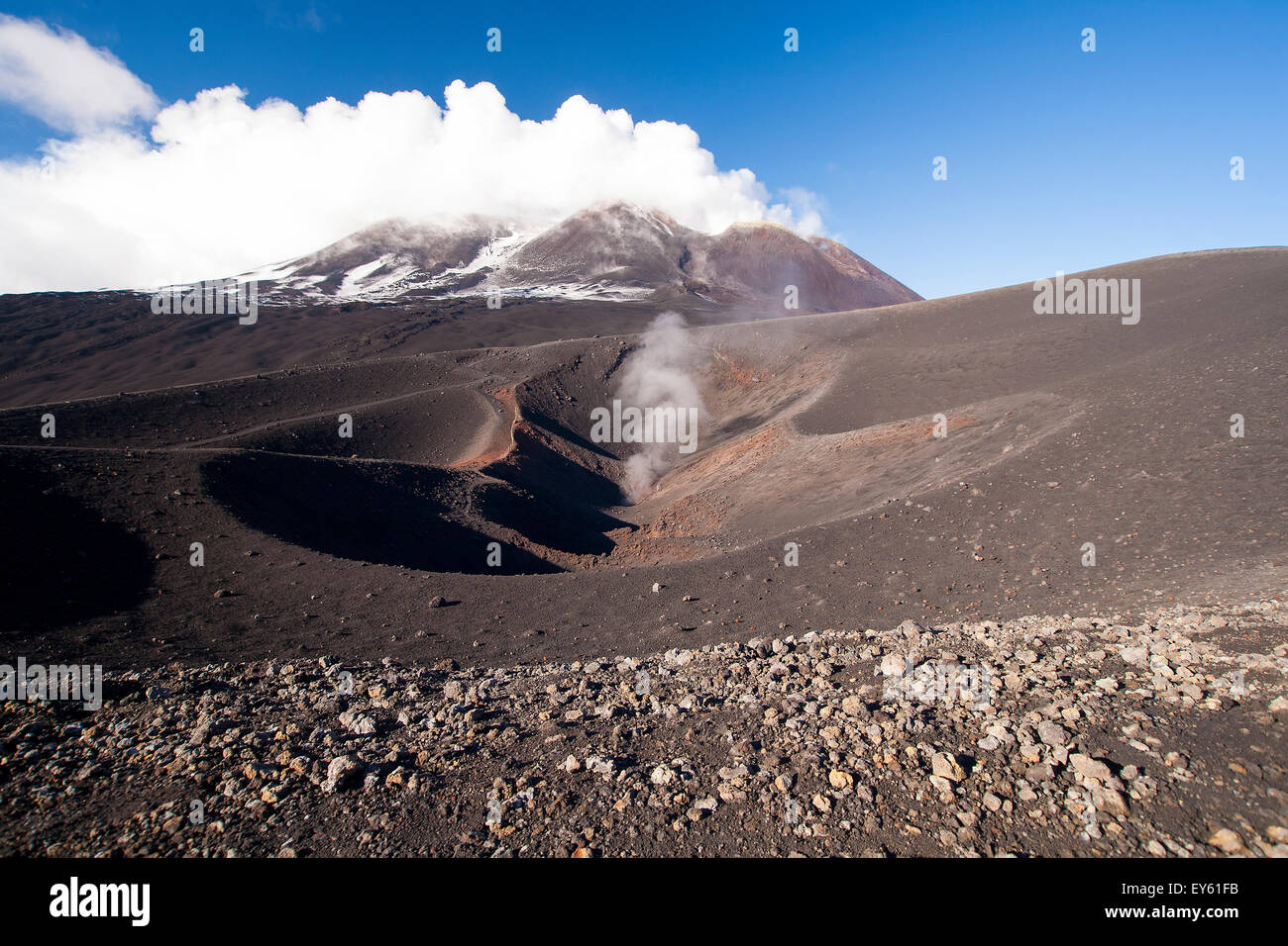 Volcano smoking crater on side of Mount Etna Sicily Italy in black lava field. Stock Photo