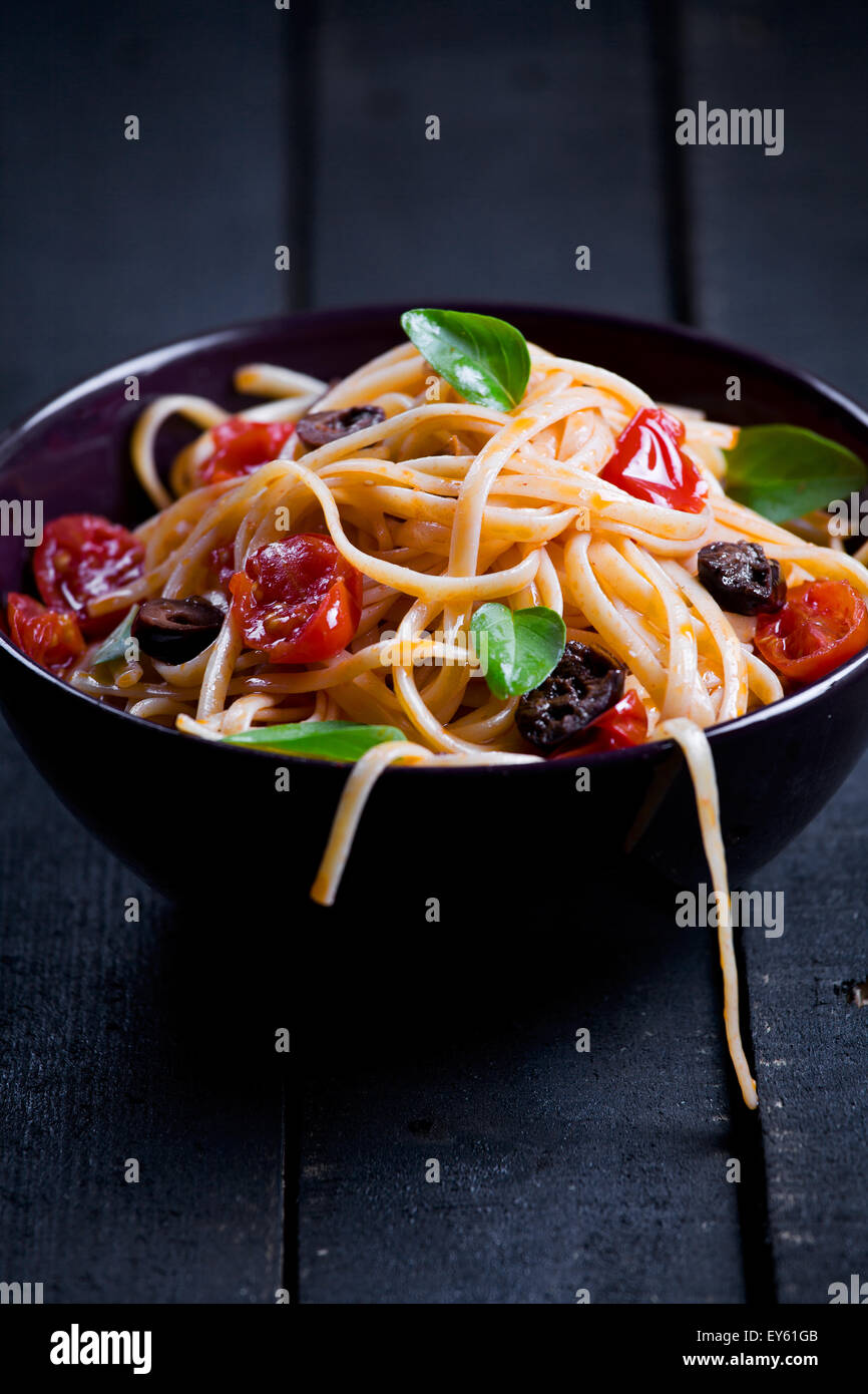 Close up of some pasta with tomatoes olives and basil - Stock Image