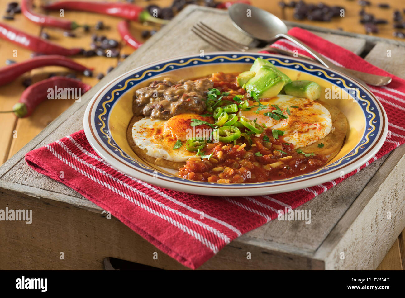 Huevos rancheros. Fried eggs on tortillas with tomato chilli sauce and refried beans - Stock Image