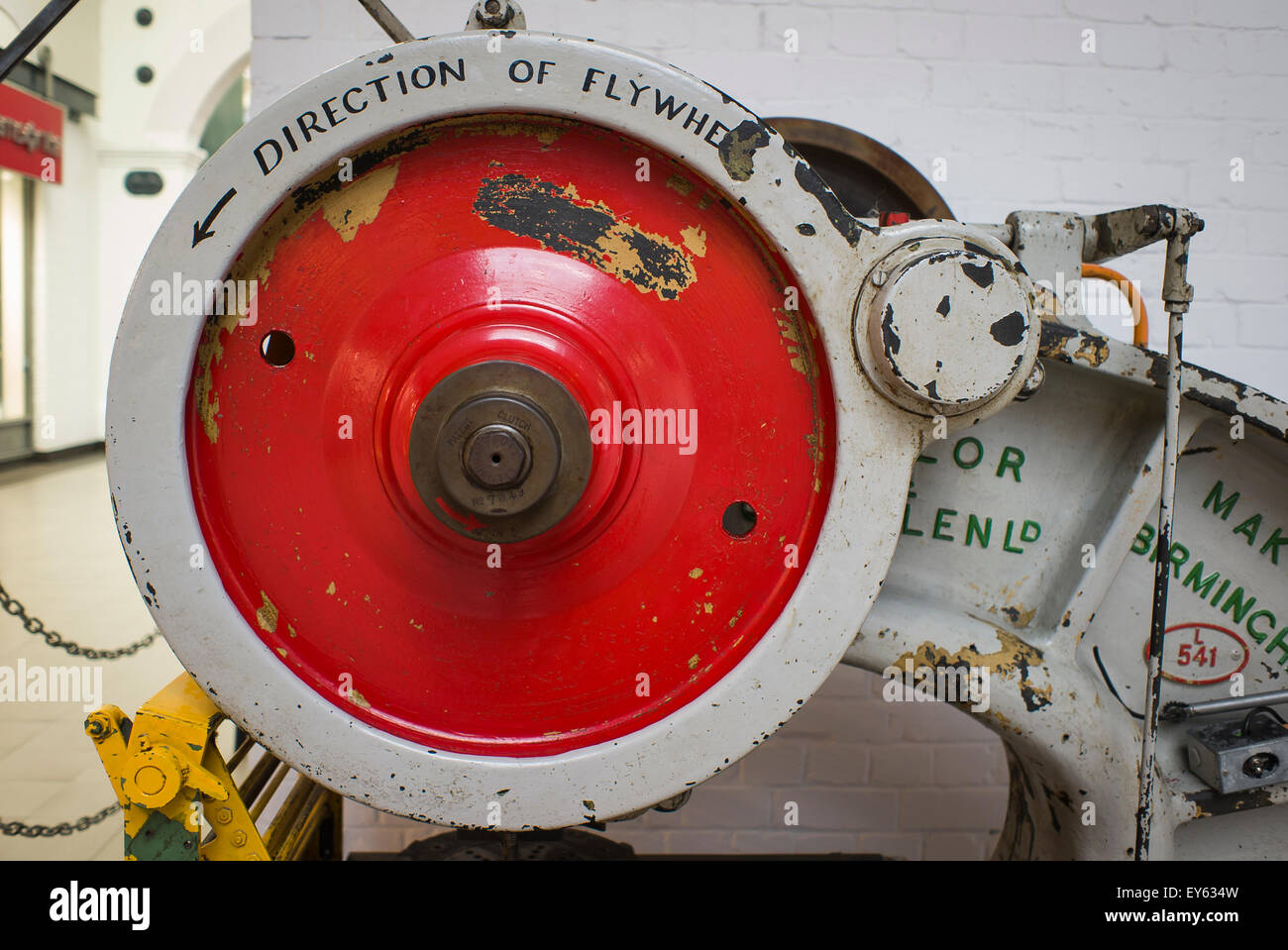 Heavy metal flywheel on old industrial machine exhibited in shopping mall in UK - Stock Image