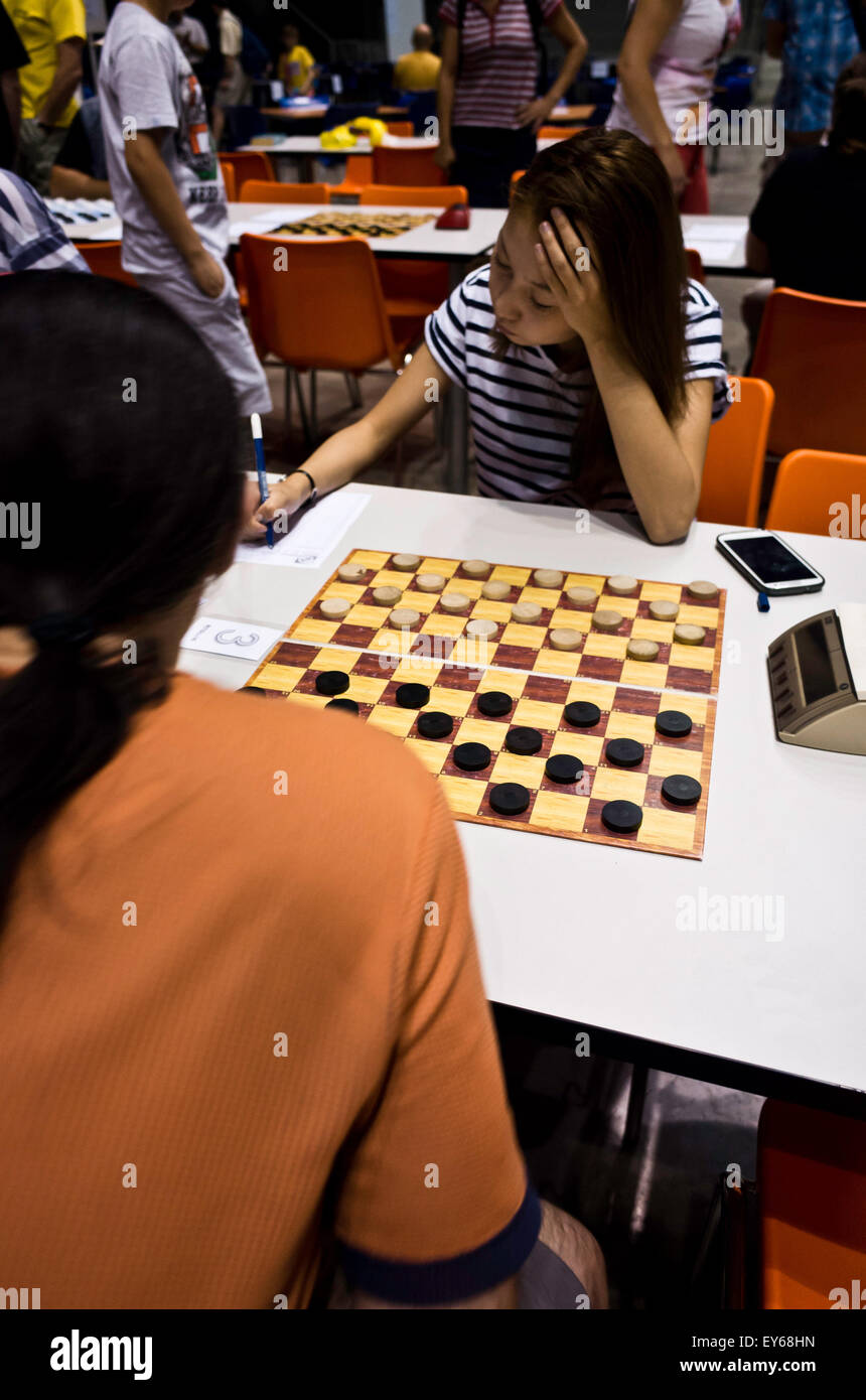girl playing draughts in a tournament - Stock Image