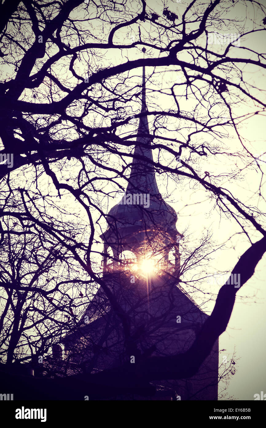 Vintage instagram filtered photo of mysterious or scary church bell tower silhouette at sunset. - Stock Image