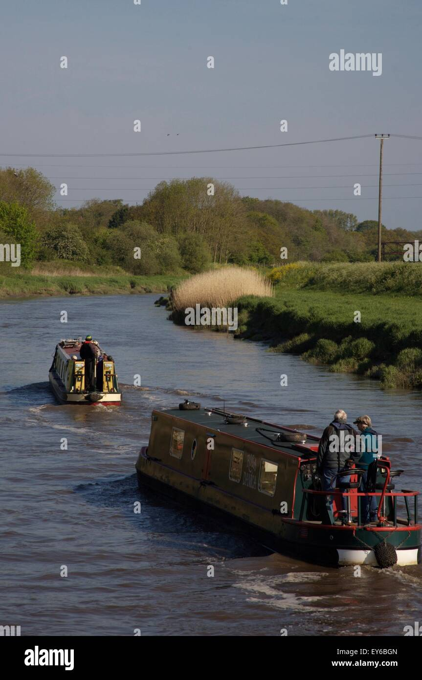 narrowboats cruising down the River Douglas, on their way to join the River Ribble and the Ribble Link on to the - Stock Image