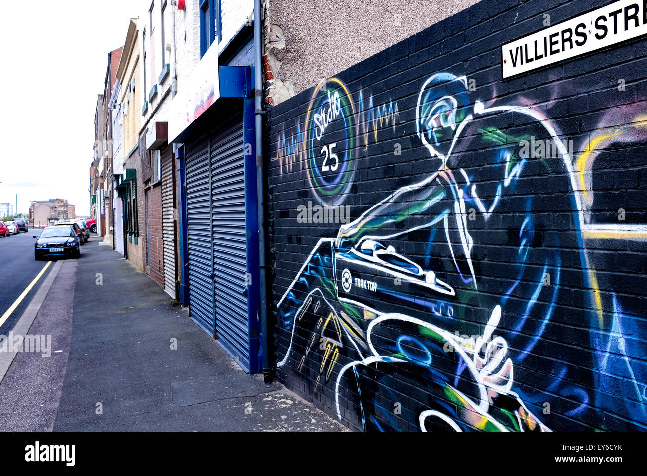 Graffiti art on a wall in Sunderland, UK depicts a DJ playing records. - Stock Image