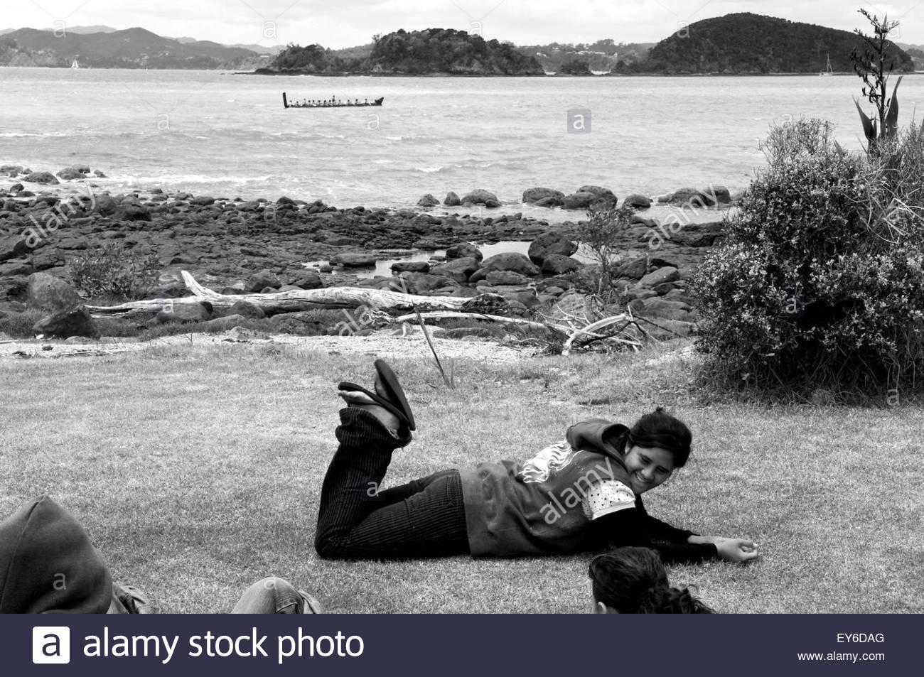 In the distance, a waka (traditional Maori canoe) participates in Waitangi Day annual commemorations on Waitangi - Stock Image