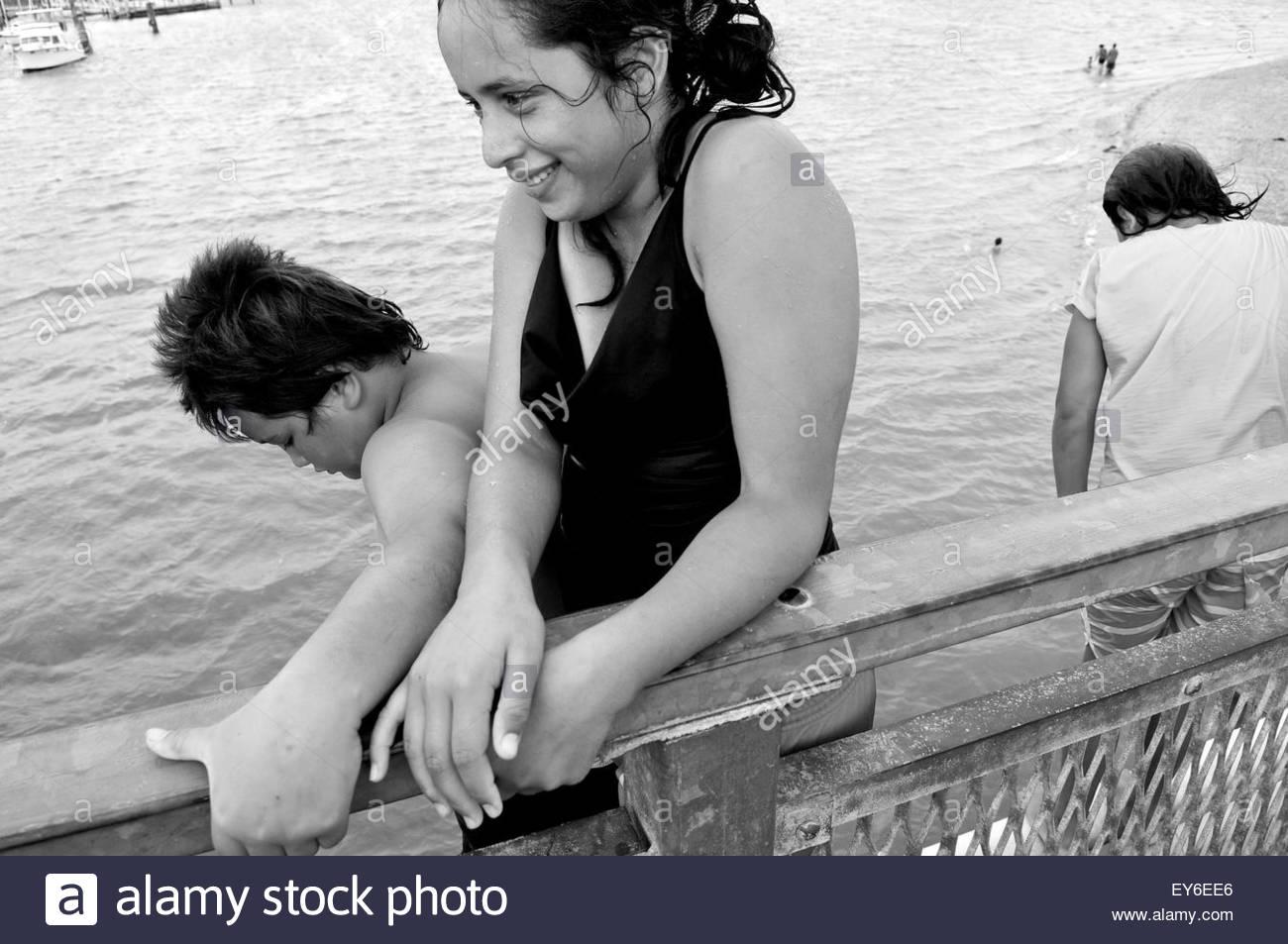A group of Maori children dive from the bridge near Waitangi Treaty House, Bay of Islands, North Island, New Zealand - Stock Image