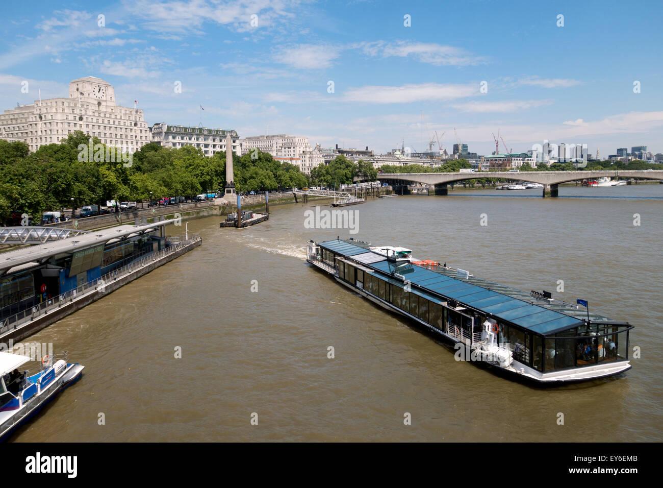A tourist sightseeing boat leaving Embankment Pier, River Thames, London UK - Stock Image