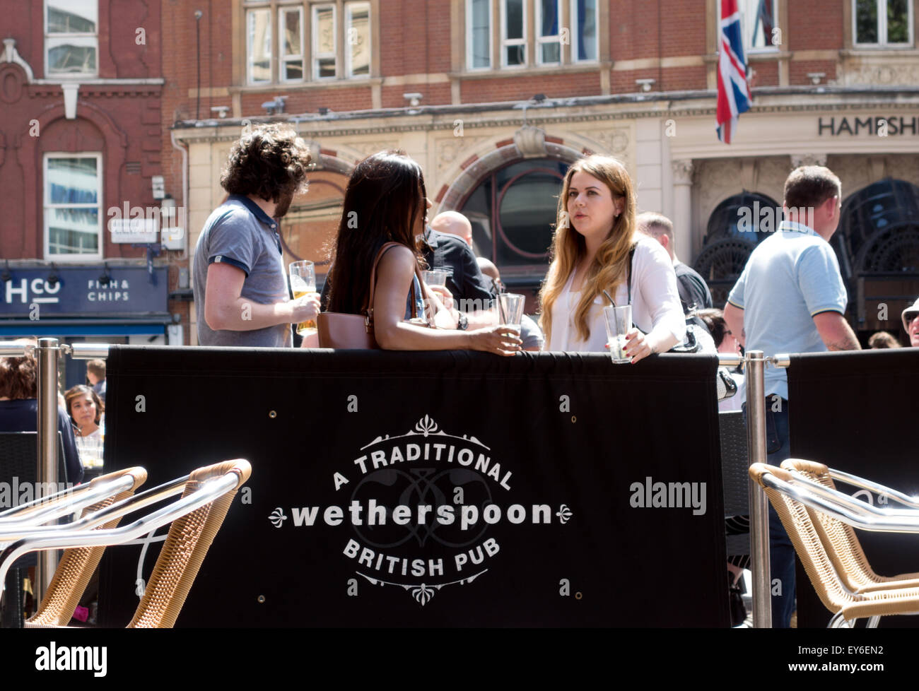 People drinking at the Moon Under Water, a Wetherspoons Pub, Leicester Square, London, UK - Stock Image