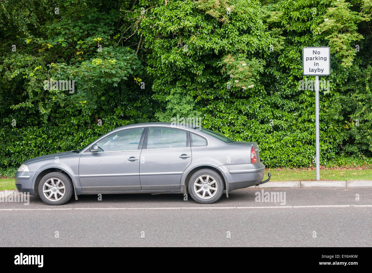 Car parked in a layby despite sign saying 'No parking in layby' - Stock Image