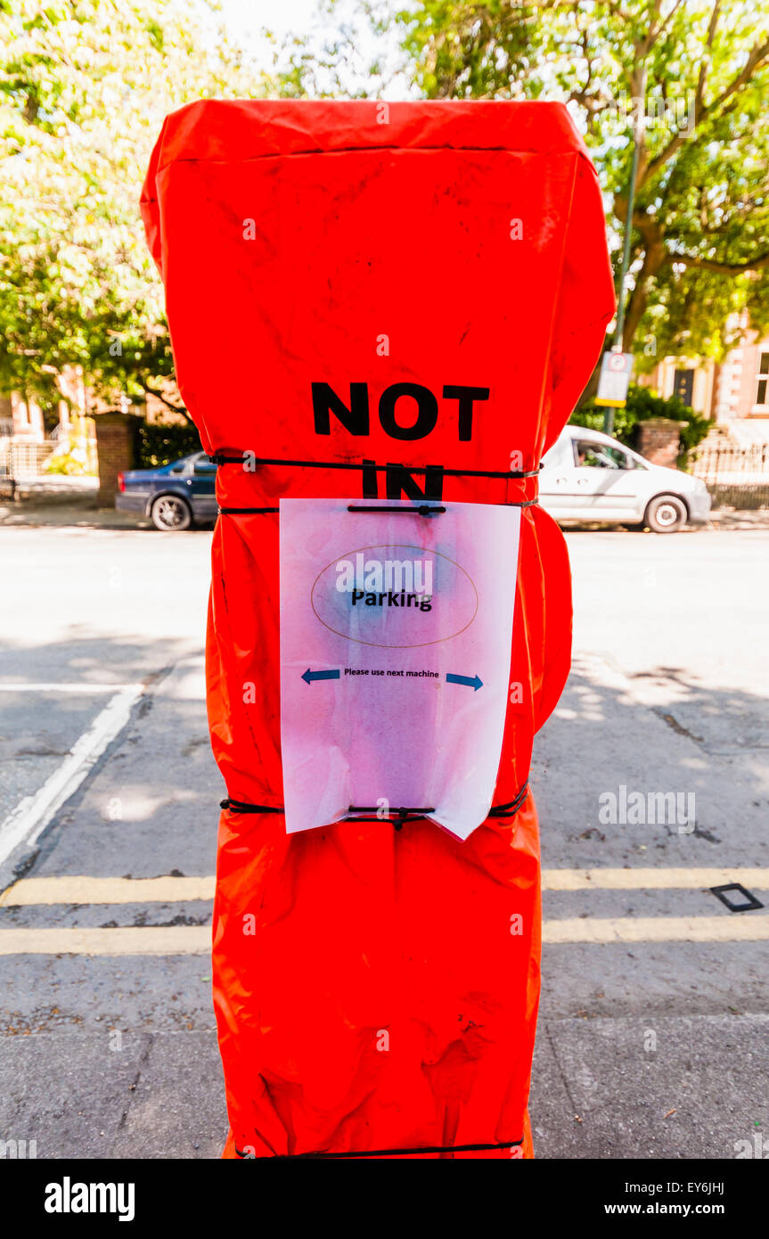 Out of order parking meter with high visibility cover, and note pointing to other signs. - Stock Image