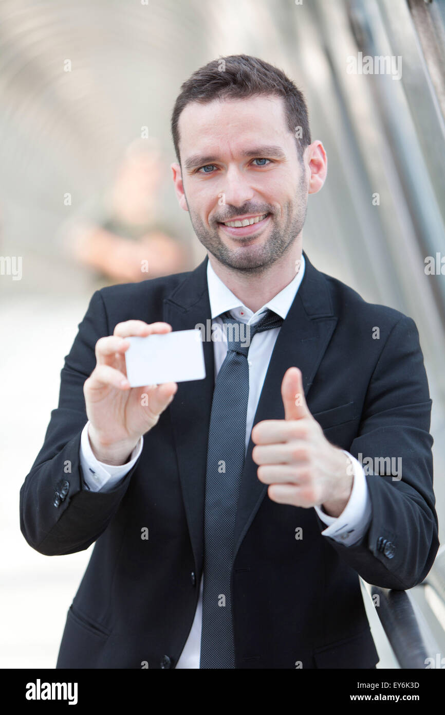 View of an Attractive businessman showing an empty textspace card - Stock Image