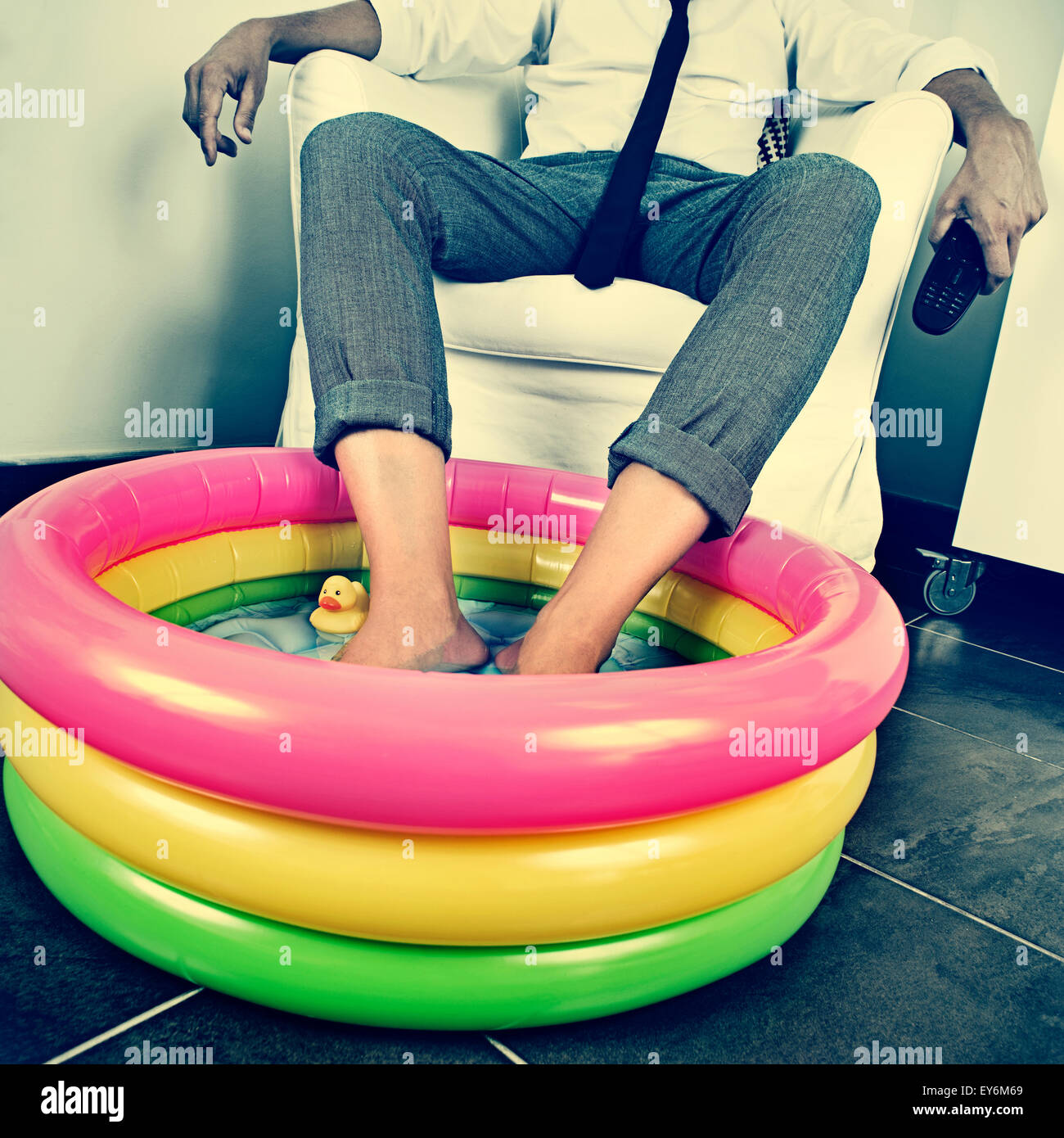 a young man in suit soaking his feet in an inflatable water pool indoors, with a dramatic effect, depicting the - Stock Image