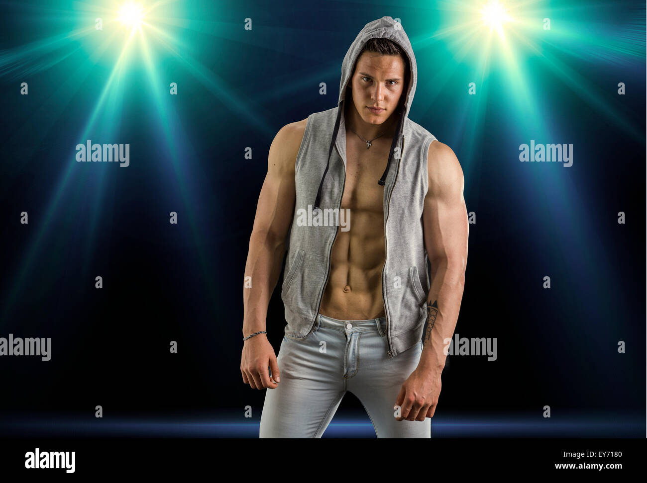 Confident, attractive young man with open vest on muscular torso, ripped abs and pecs. On dark background with spotlights - Stock Image