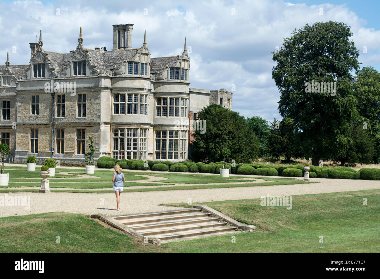 Female visitor listens to the audio guide in the formal gardens at Kirby Hall Kirby Hall, Northamptonshire, UK - Stock Image