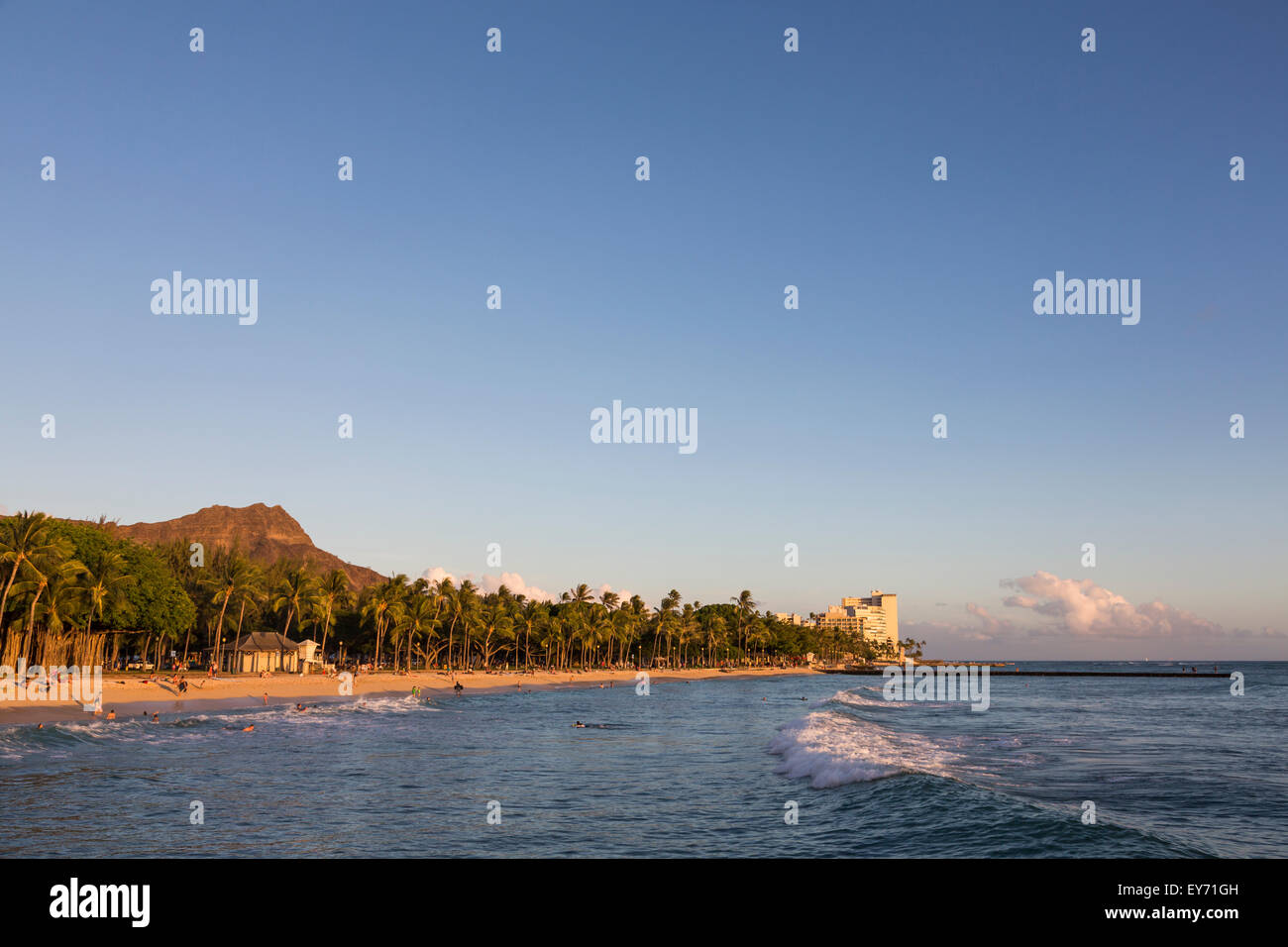 Queen's Surf Beach in Waikiki with a view Diamond Head at sunset. - Stock Image