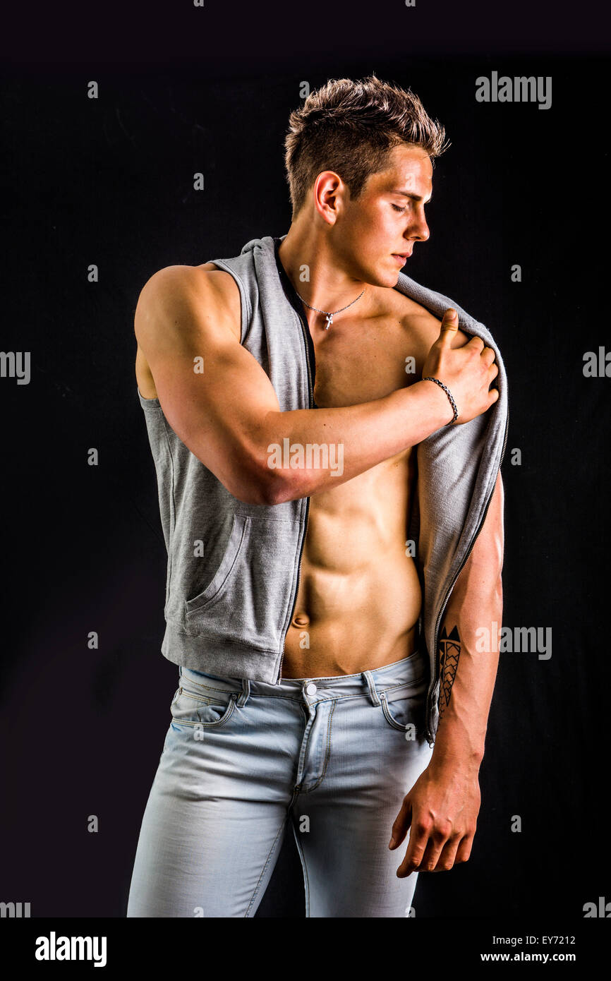 Confident, attractive young man with open vest on muscular torso, ripped abs and pecs. Isolated on black - Stock Image