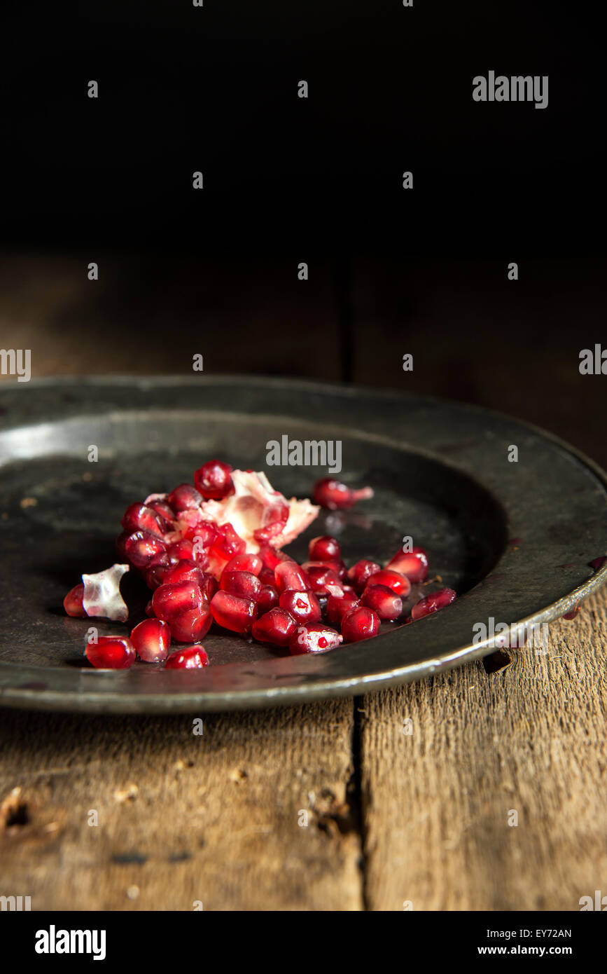 Moody natrual lighting images of fresh juicy pomegranate with vintage style - Stock Image