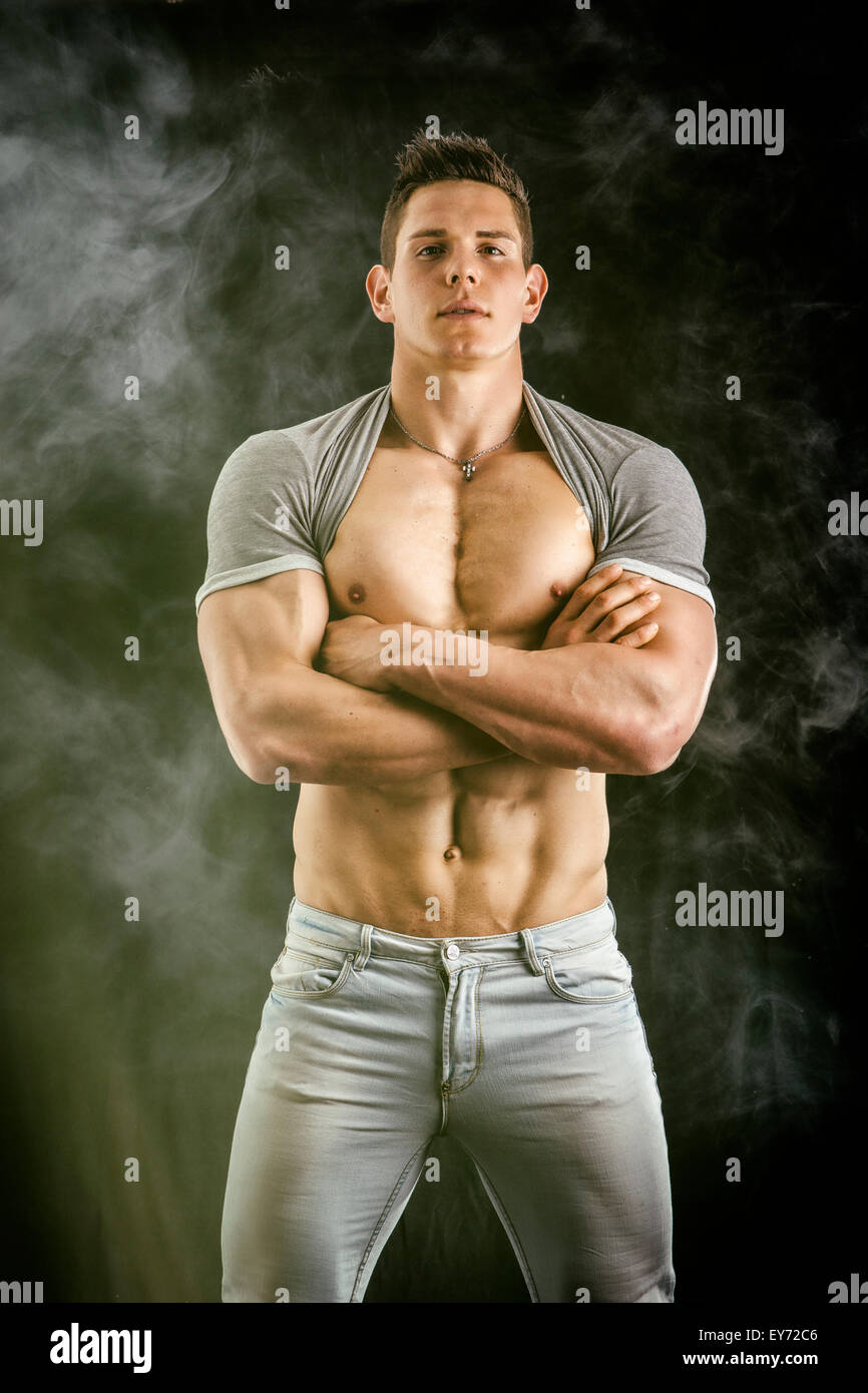 Confident, attractive young man with open vest on muscular torso, ripped abs and pecs. On dark background - Stock Image