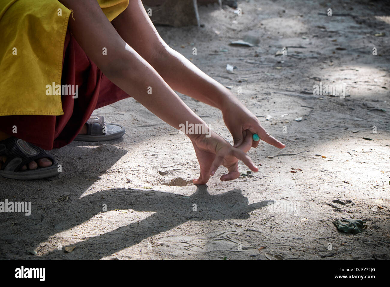 Asian marbles game and shooting technique. Thailand S. E. Asia - Stock Image