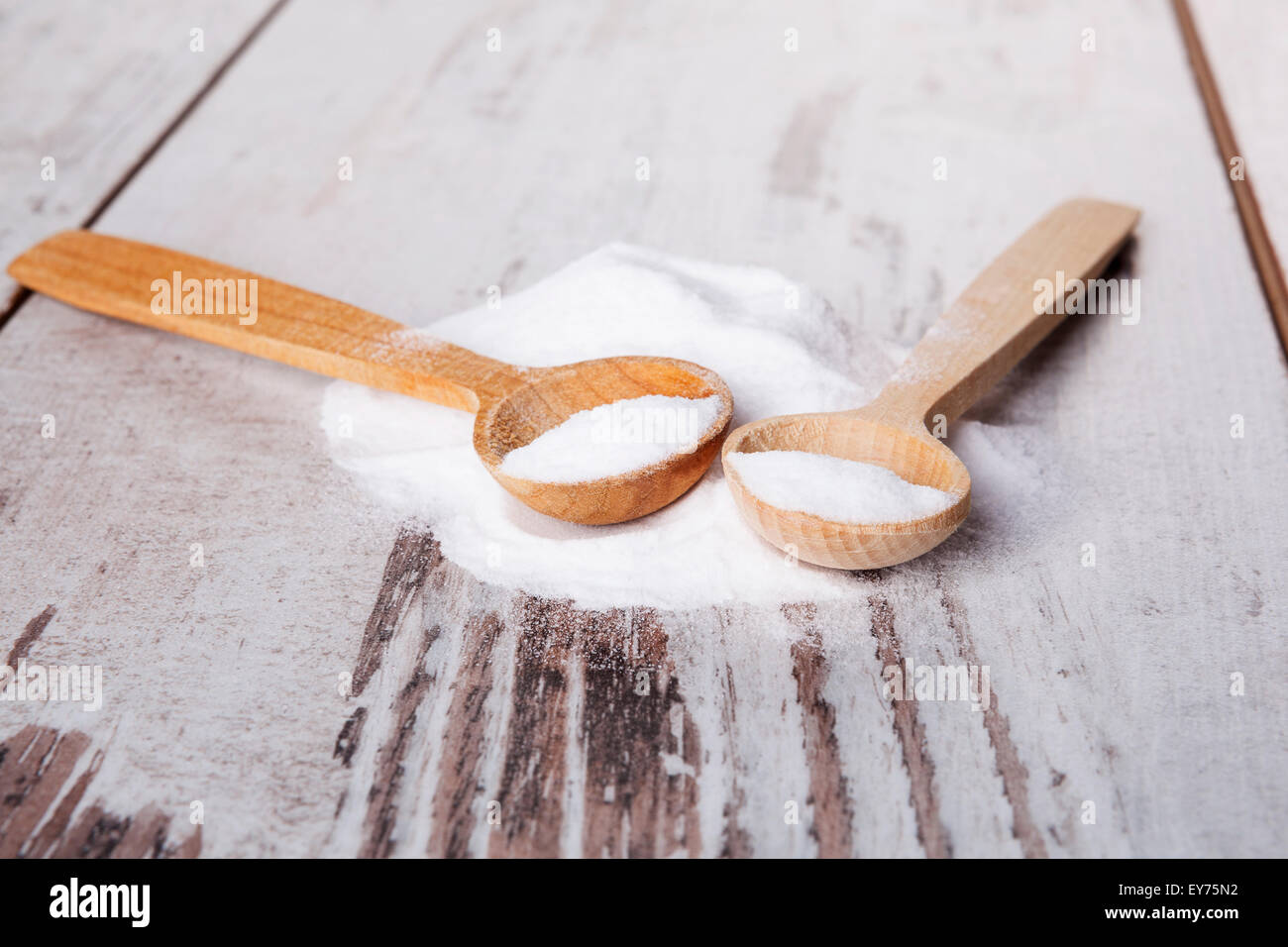 Baking soda on wooden spoon on white wooden textured background. - Stock Image