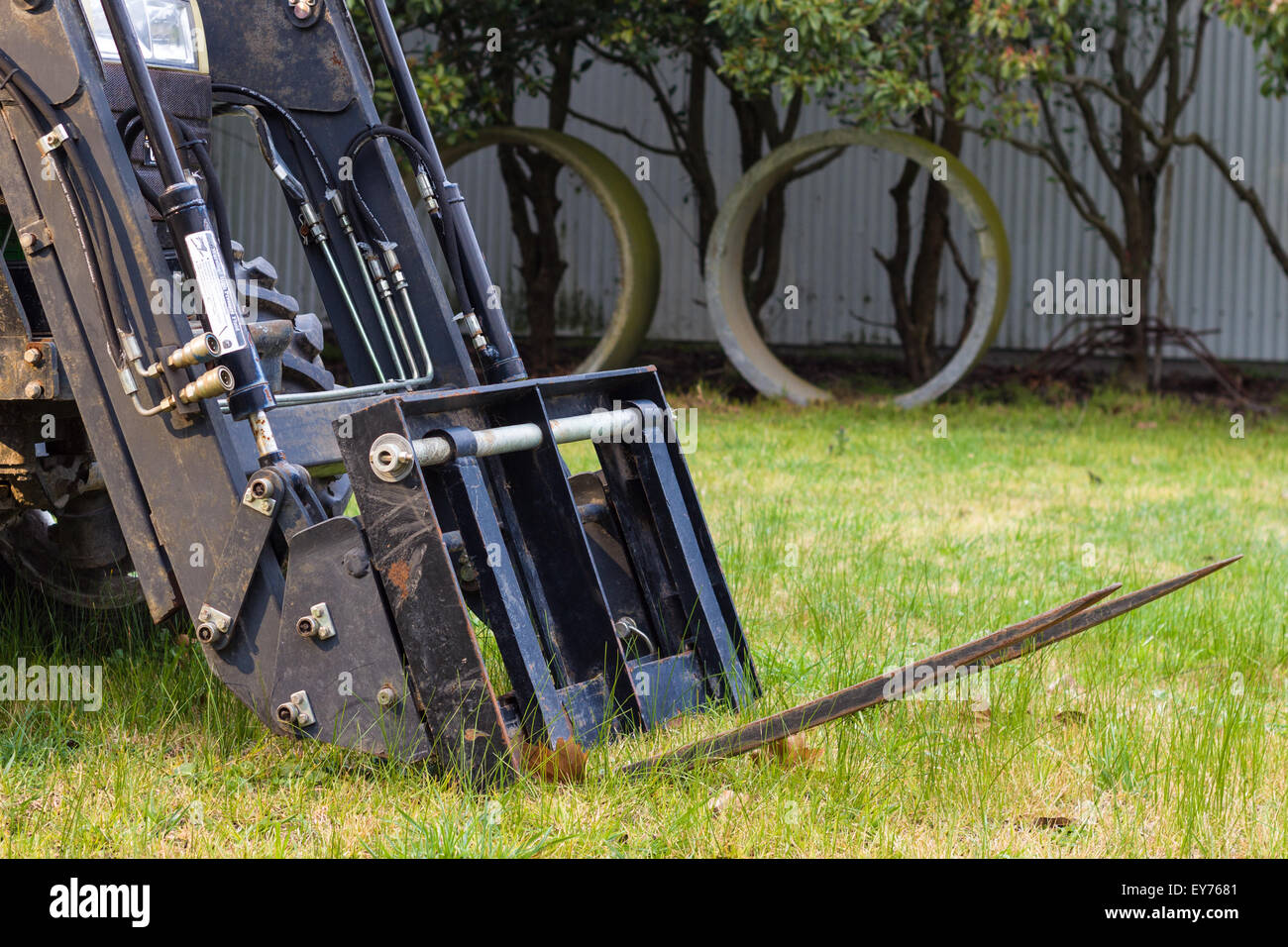 Front end loader with a forklift attachment fitted to a small tractor on green grass - Stock Image