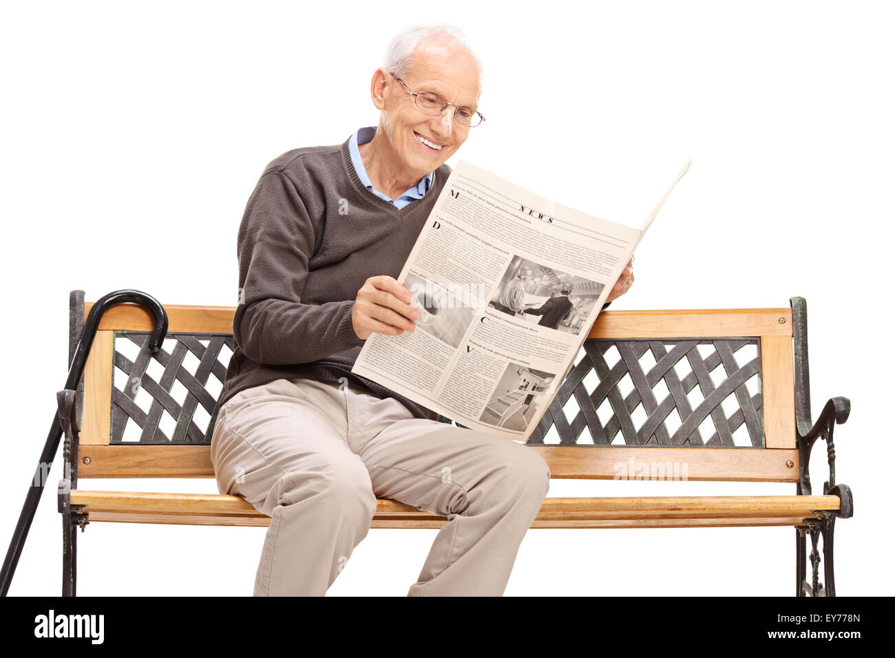 senior man reading a newspaper seated on a wooden bench isolated on