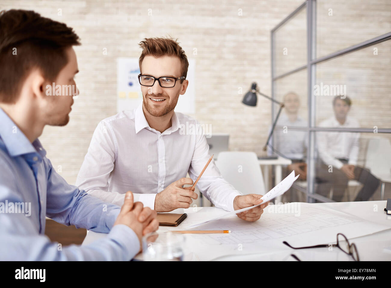 Young businessman in eyeglasses talking to his co-worker at meeting - Stock Image