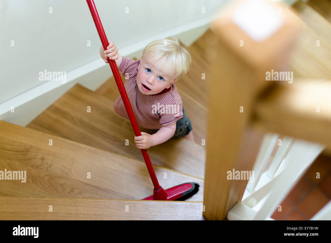 Young boy, 2 years, sweeping a staircase with a broom. - Stock Image