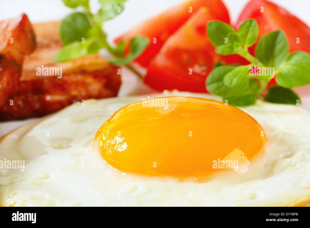 Pan-fried meatloaf with sunny side up fried egg - Stock Image