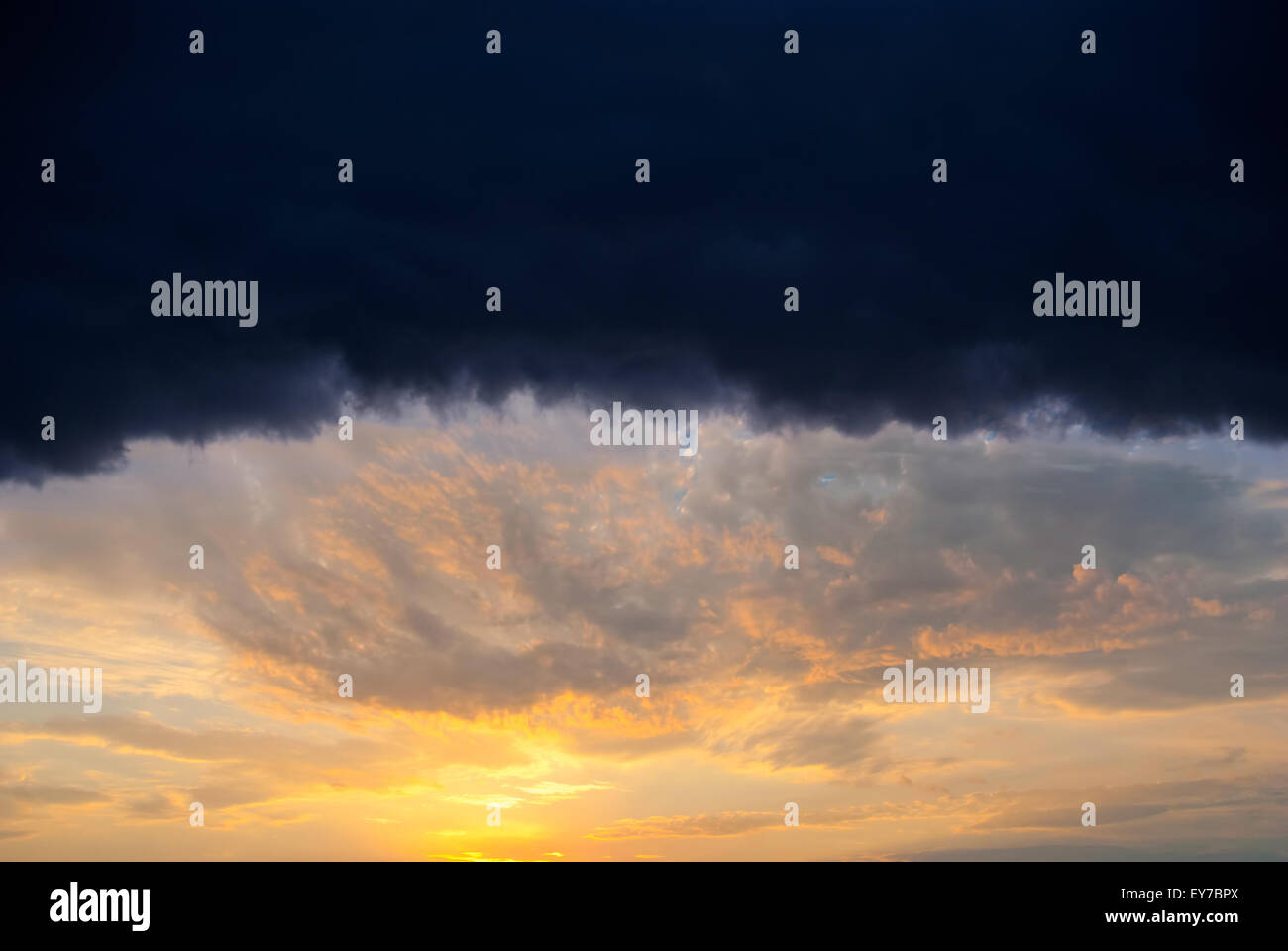Huge rain cloud lit orange sunset - Stock Image