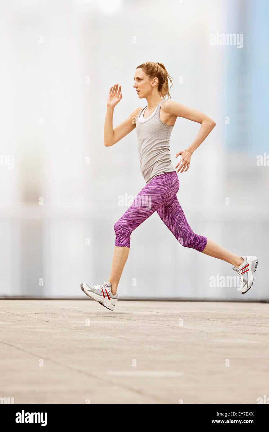 Mid adult woman running - Stock Image