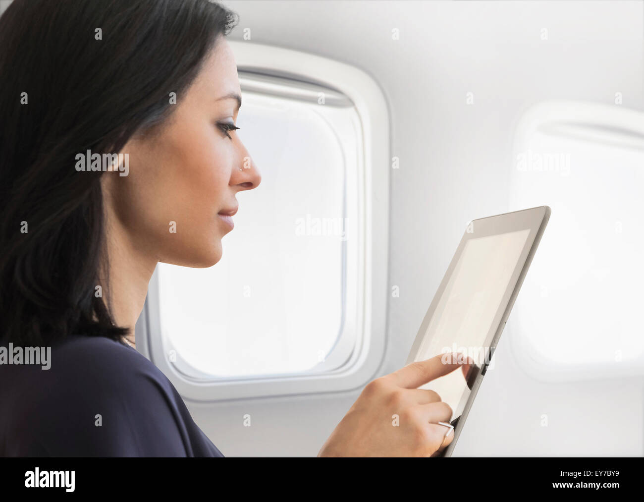 Young woman using tablet on plane - Stock Image