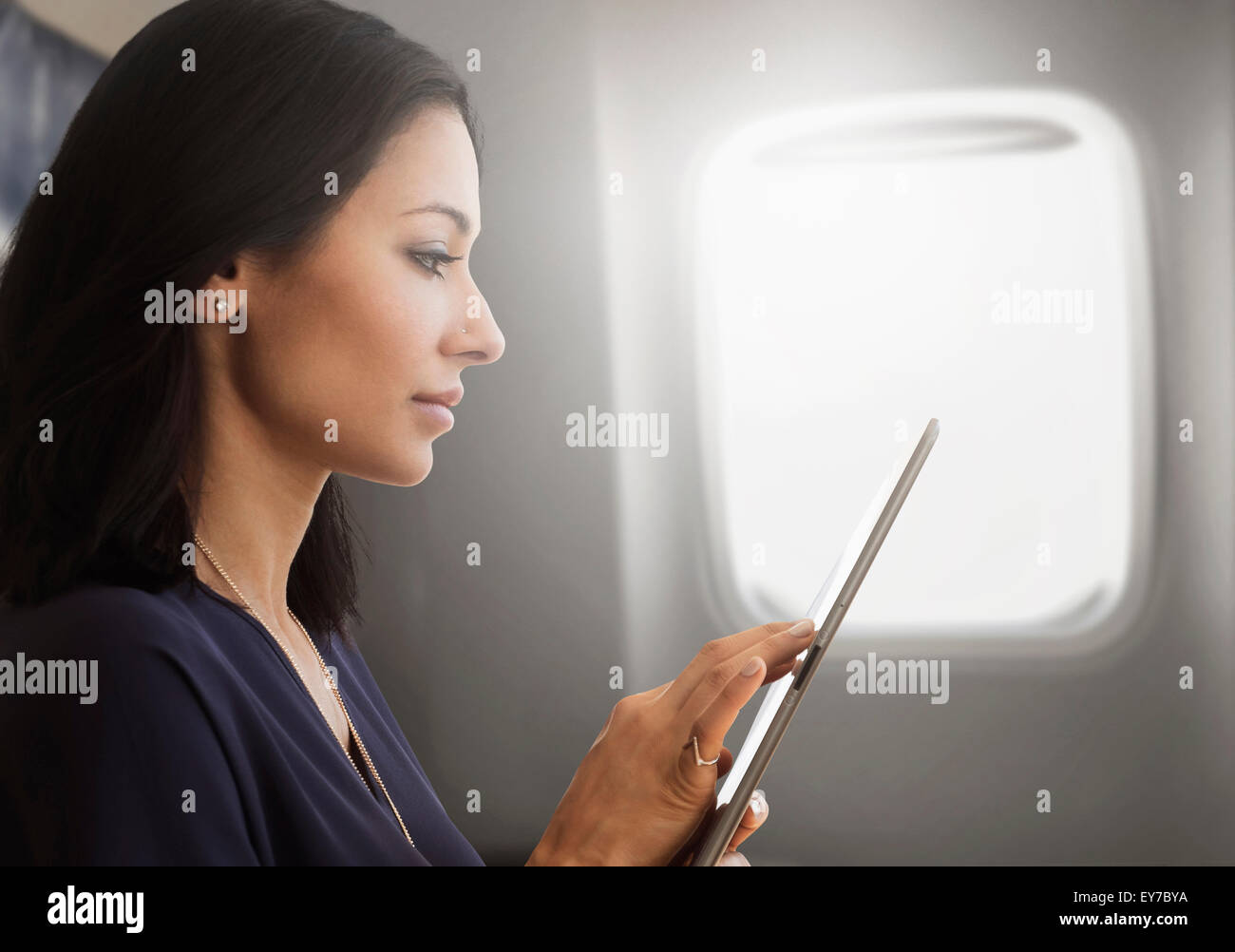 Young woman using tablet on plane Stock Photo