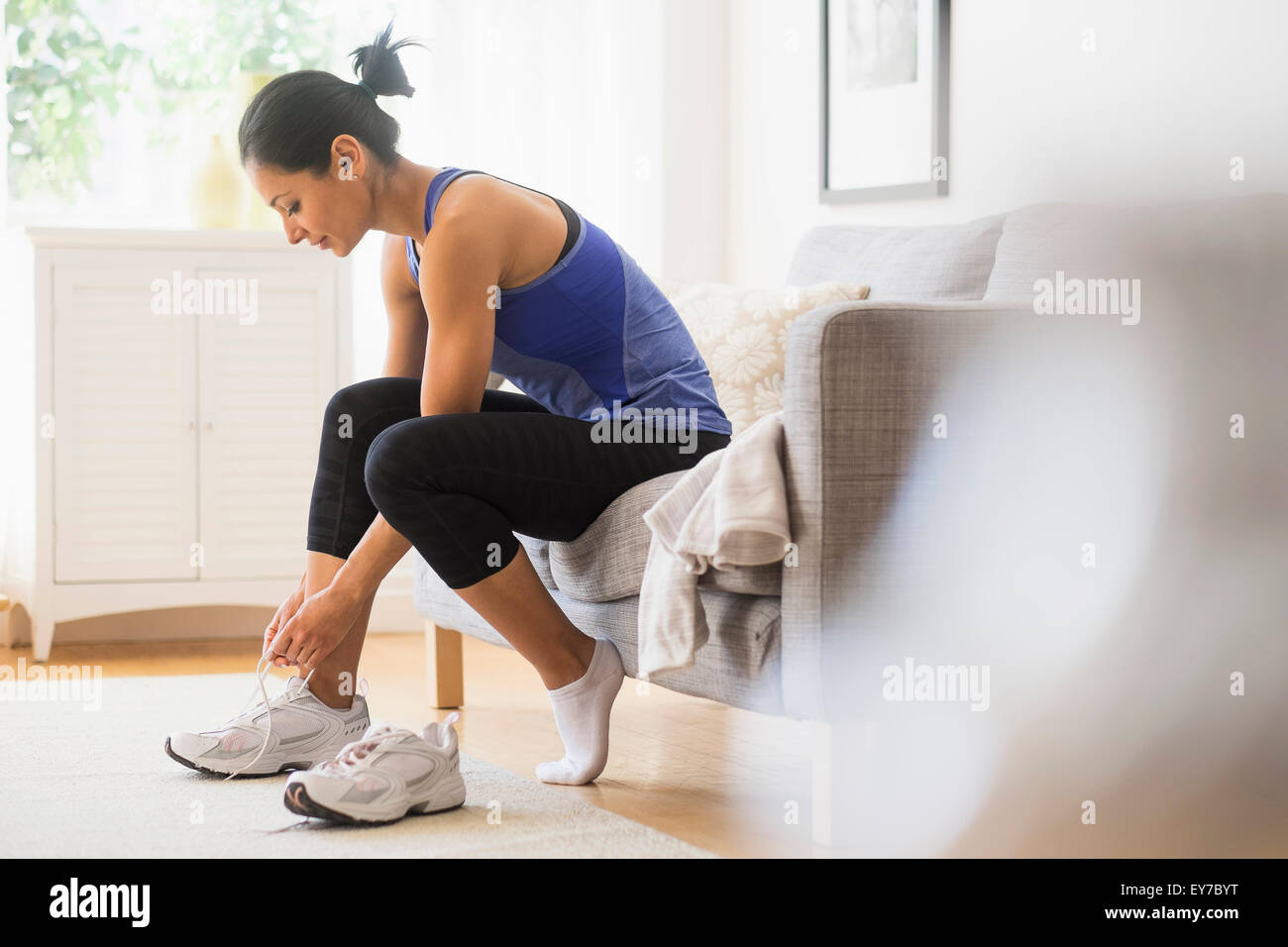Young woman putting on shoes - Stock Image