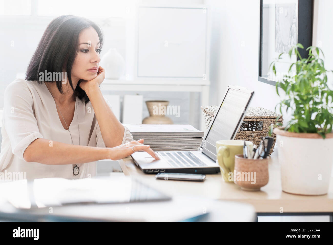 Woman sitting at desk with laptop - Stock Image