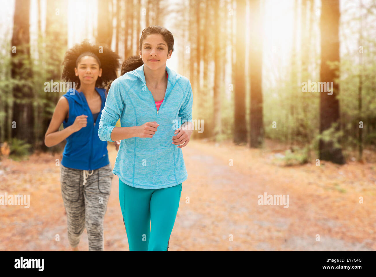 Portrait of teenage girls (14-15, 16-17) running - Stock Image