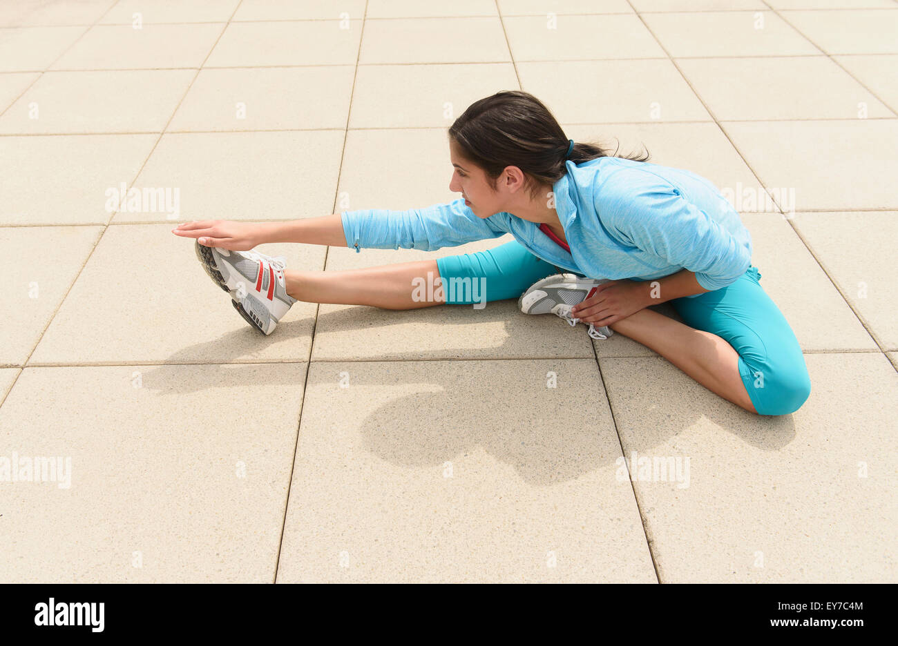Teenage girl (14-15) stretching - Stock Image