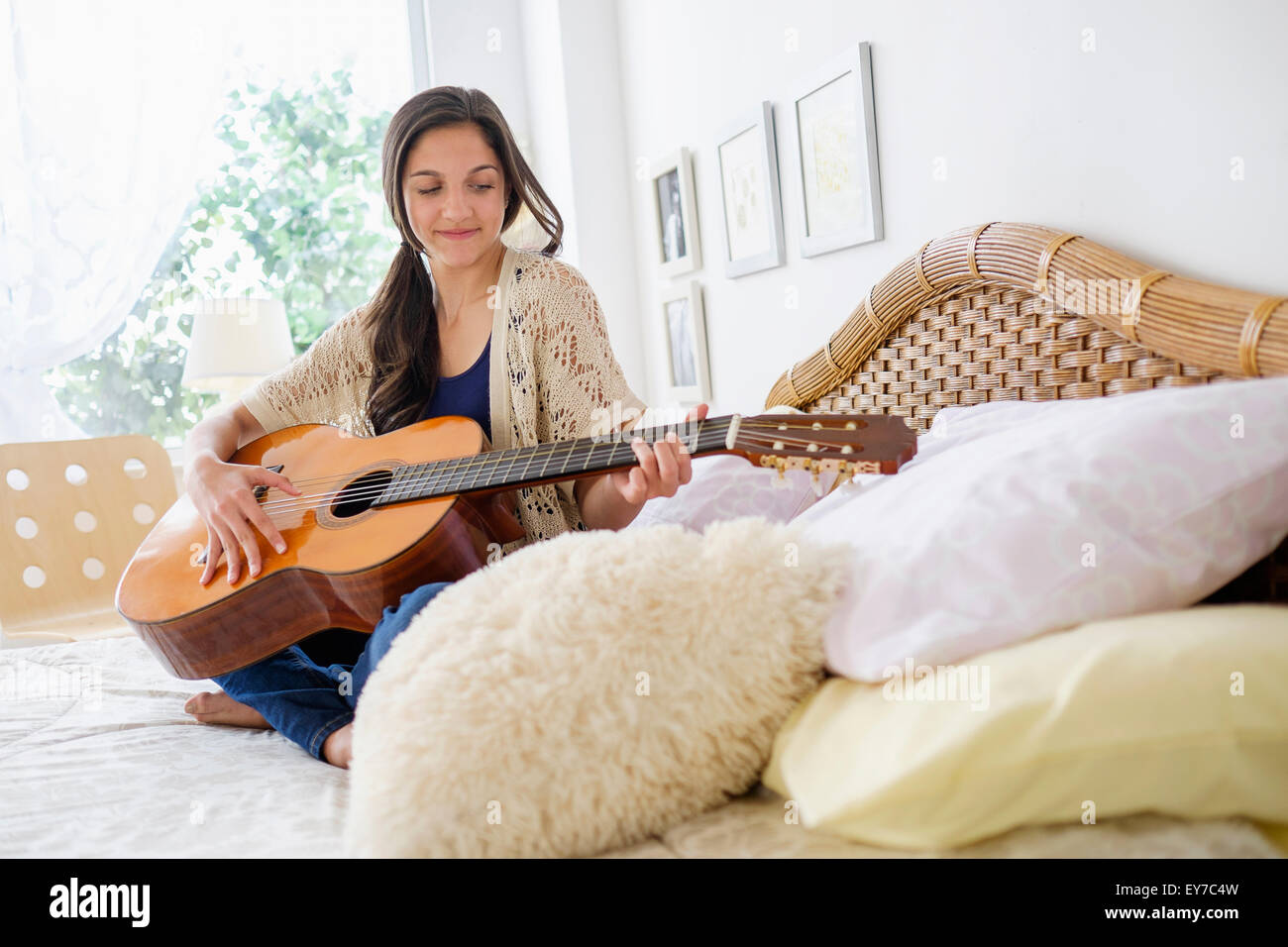Teenage girl (14-15) playing guitar - Stock Image