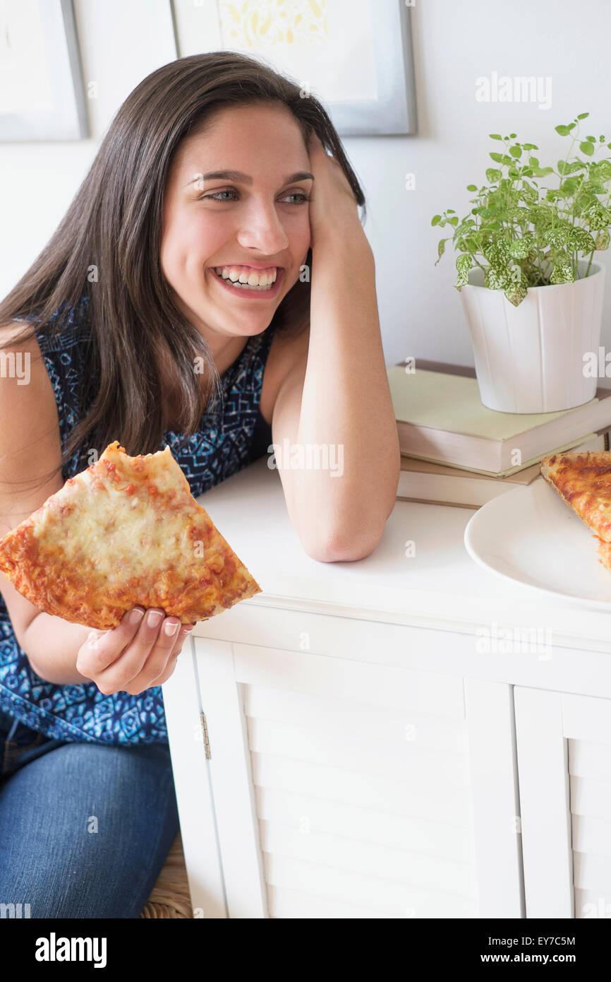 Teenage girl (14-15) eating pizza - Stock Image