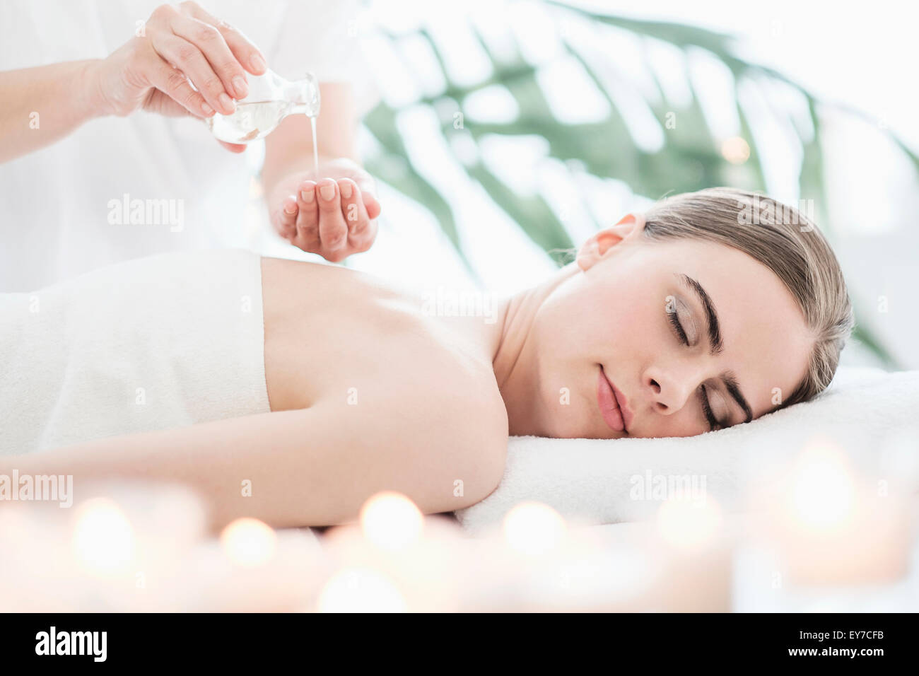 Therapist putting massaging oil on young woman in spa - Stock Image