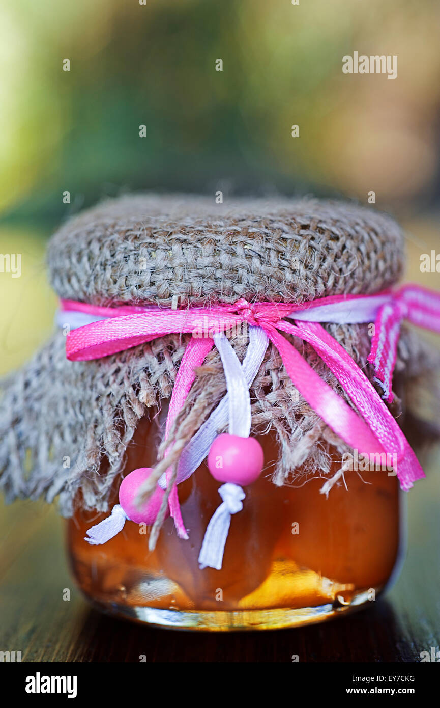 Decorative jar with preserved apricots in syrup - Stock Image