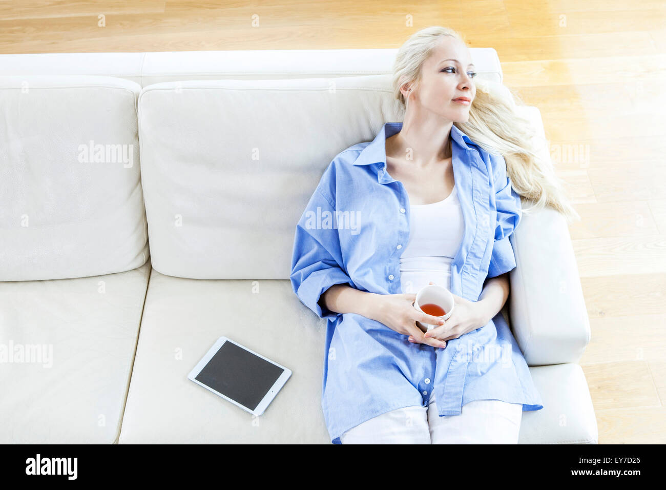 Blond woman sits on sofa day dreaming - Stock Image